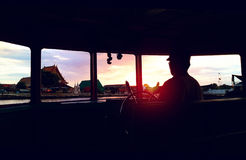 Sunset Bangkok riverside view from silhouetted boat& x27;s window Stock Images