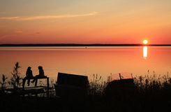 Sunset on the bank of lake. Girls sit on the bank of lake on a sunset Royalty Free Stock Photography