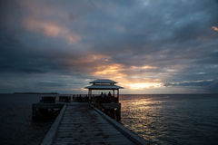 Sunset and Bar at Tropical Resort. A beautiful sunset silhouettes a bar at the end of a resort pier in Wakatobi National Park, Indonesia. This area, south of Stock Images