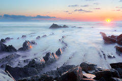 Sunset in barrika coast with water and rocks Royalty Free Stock Photography