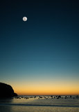 Sunset bay with moon. Sunset view of bay with fishing boats with full moon above Royalty Free Stock Image