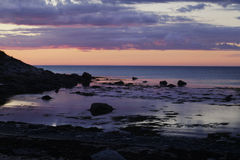 Sunset in the bay. Pink Blue Sunset in the bay near the cliff Royalty Free Stock Image