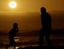 Sunset at the beach. Father and son enjoying the last rays of the sun Stock Photos