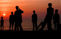Sunset on the Beach. Silhouettes on the beach as the sun sets Royalty Free Stock Image
