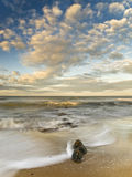 Sunset at the Beach. Sunset seascape in a beautiful sandy beach, with a rock on the foreground Stock Image