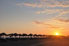 Sunset on beach. Umbrella on sandy sea beach at sunset stock photo Stock Photography