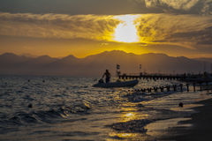 Sunset at beach. A speedboat is coming to shore, people swimming during the sunset and the others are standing on the pier Royalty Free Stock Photography
