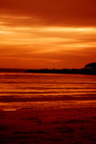 Sunset at the beach. A sunset at the beach. The land and trees along the coast are black from the lighting, appearing only as silhouettes Royalty Free Stock Photos