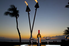 Sunset on the Beach. A bottle of wine and two glasses awaits turists on a beachside table at sunset stock images