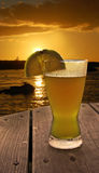 Sunset at the Beach Bar. Frosty and refreshing beer glass with orange slice sitting on a wood table overlooking the ocean and sunset Stock Photos