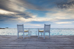 Sunset at beach bar. Lonely chairs on beach bar, malediven Royalty Free Stock Photo