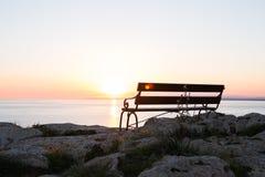Sunset beach and bench Stock Photos