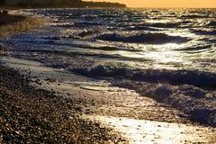 Sunset on the beach with black sand. Aegean sea, pebble Stock Photo
