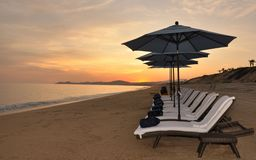 Sunset with beach chairs. Beach chairs and umbrellas in front of sunset at the beach stock photo