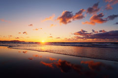 Sunset on beach with cloud reflections Royalty Free Stock Photo
