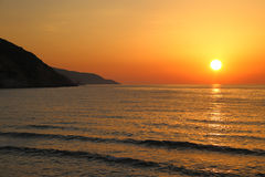Sunset on the beach with distant mountains Royalty Free Stock Images