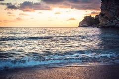 Sunset beach with dramatic orange sky and cliffs on Montenegro seashore Stock Photos