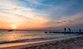 Sunset Beach in early spring with young males posing for photos in distance - Cape May Point NJ. Selfie, portrait, fun royalty free stock photo
