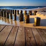 Sunset on the beach and empty wooden deck table. Royalty Free Stock Photography