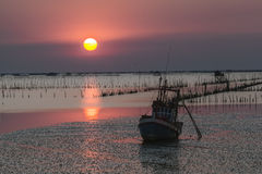 Sunset beach and fishing boat Stock Images