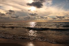 Sunset at the beach of Gallipoli. Sunset in Gallipoli beach with clouds and small waves - Italy Stock Photography