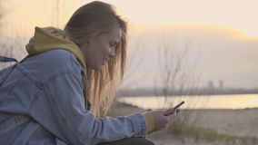 Sunset beach and girl using smartphone for chatting. Nature and technologies. Young woman chatting hold in hand cellphone slow motion. Female hiker smile by the stock video