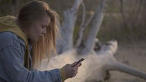Sunset beach and girl using smartphone for chatting. Nature and technologies. Young woman sitting on the beach on the broken tree and chatting holding in hand stock video