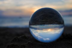 Sunset on Beach in Hawaii Captured in Glass Ball. Sunset at beach with sky sun sand and sea captured in glass ball royalty free stock photos