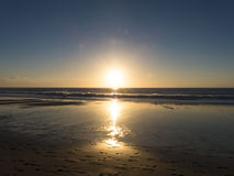 Sunset at the beach with intense glowing orange, yellow, red col Royalty Free Stock Photo