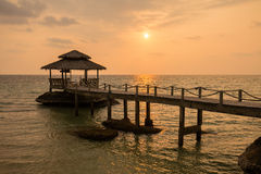 Sunset on the beach. Island Koh Kood, Thailand. Tropical sand beach with pier near sea water on the sunset Stock Images