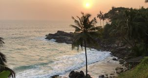 Sunset on the beach of Kerala. Golden evening sunset over the beach with waves of water crashing on the rocks and gentle breeze moving palm tree leaves stock video footage