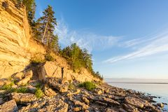 Sunset on the beach. Limestone cliff in the sea under blue sky and white clouds Royalty Free Stock Image