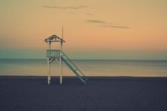Sunset at a Beach Loneliness. A calm sea and a calm beach with an empty hut which express loneliness Royalty Free Stock Image