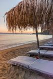 Beach lounge at sunset. Sunset at the beach with lounge chairs and reed umbrellas, Skiathos island, Greece, 2018 stock images