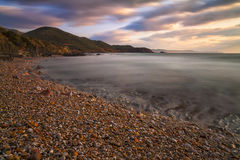 Sunset on the beach of pebbles. The picture shows a spring sunset beach of Masua located in Sulcis Iglesiente Stock Photos