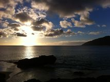Sunset on a beach. This photo was taken at Makua Beach on Oahu, Hawaii. The westside of the island is known for their glistening waters as if there are diamond Stock Image