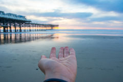 Sunset on the beach with a pier. Blue and orange sunset. Sun on the hair. Sunset on the beach with a pier. Blue and orange sunset. Sun on the hand. California stock images