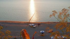 Sunset beach with recreational boats and sun flares on sea surface stock video footage