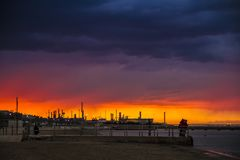 A sunset in a beach with a refinery in the background. A sunset inthe Falconara Marittima`s  beach with a refinery in the background, Ancona Stock Photography