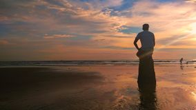Sunset on the beach. SABAH, MALAYSIA - JULY 6, 2017 : A man was sitting on the rock with majestic view of `Pantai Manis` beach Royalty Free Stock Image