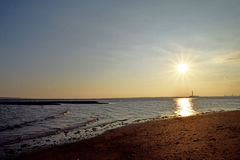 Sunset at the beach. Sunset at the seashore showing the sun's rays and the sun reflected in the sea Stock Photo