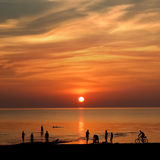 Sunset on the beach. The setting sun on the bay and the shadows of people Royalty Free Stock Photos