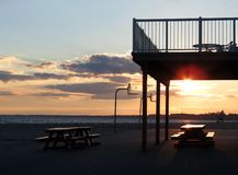 Sunset on the Beach. The setting sun reflects off a picnic table under a balcony on the beach royalty free stock photos