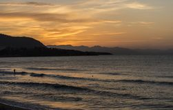 Sunset on the beach in Sicily. Shortly after sunset on a beach in Sicily. A blazing orange sky and equally textured mediterranean sea with soft waves stock photo