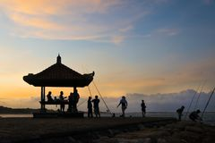 Sunset on the beach, silhouette hut and a few people stock image