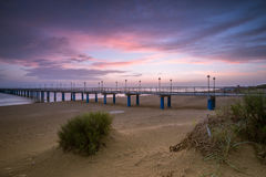 Sunset on the beach after a storm, the pier and the in the evening Royalty Free Stock Image