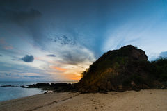 Sunset beach. Sun hiding behind a huge rock in a beautiful evening Royalty Free Stock Images