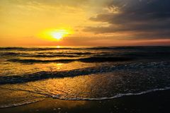 Sunset on the North Sea coast. Sunset on the beach. The sun sets in the sea. Sunset on the North Sea coast. Bright sunset golden waves royalty free stock image
