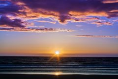 Sunset at the beach. Sunset or sundown is the daily disappearance of the Sun below the horizon as a result of Earth`s rotation. The Sun will set exactly due west Royalty Free Stock Images