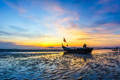 Sunset on the beach in Trang province,Thailand. Sunset on the beach with old wooden fishing boat in Trang province,Thailand stock photo